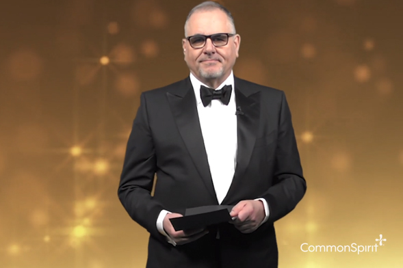 Presenter in tuxedo opens awards envelope.