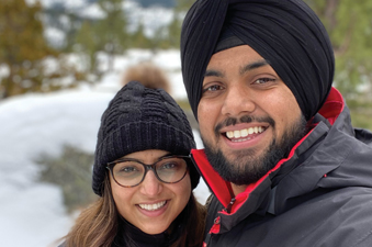 Two adults stand in a snowy landscape.
